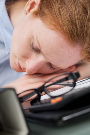articulos oficina: Imagen de detalle de una mujer de negocios que duerme entre diversos art�culos de la oficina en un escritorio. Foto de archivo