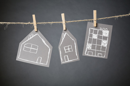 Three types of residential buildings drawn by hand on carton hanging from a rope line with clothespins.