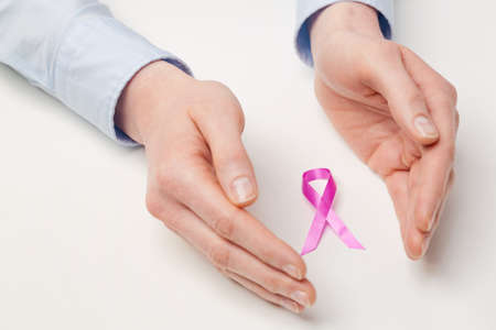 Two hands of a woman surrounding or protecting a pink ribbon - breast cancer awareness concept. photo
