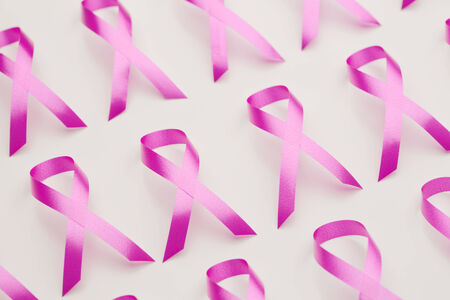 Closeup image of many pink ribbons, symbolizing awareness of female breast cancer. photo