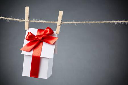 Miniature casa carta bianca con un grande nastro rosso appeso a una corda con copia spazio accanto ad essa. photo