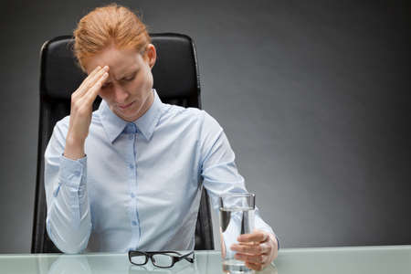 swamped: Business woman with migraine holding a glass of water. Stock Photo