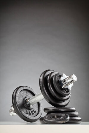 adjustable dumbbell: Vertical image of a heavy iron dumbbell resting on a stack of weight discs. Stock Photo