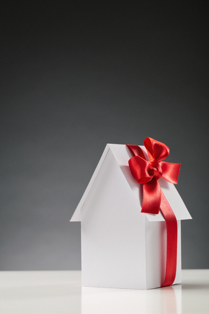 Conceptual image about property ownership, buying a new house - a white paper house with a red ribbon with copy space above it. photo