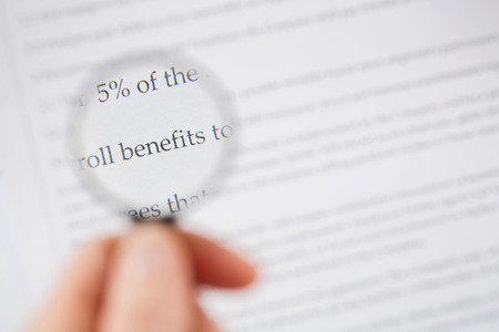 persona leyendo: Persona lectura a trav�s de la secci�n de beneficios de un contrato con una peque�a lupa.
