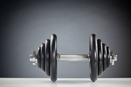 Front image of a heavy fitness dumbbell lying on a white surface.