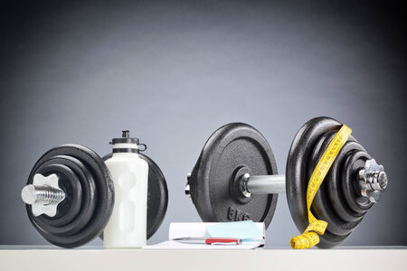 Fitness equipment and accessories next to two dumbbells. photo