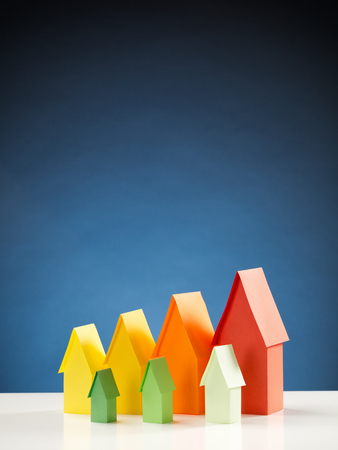 Vertical image of two rows of miniature paper houses in energy label colors with a blue background. photo