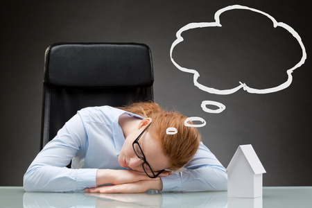 Sleeping businesswoman with a thought cloud above her head, next to a small white paper house. photo