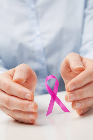 Closeup image of two hands surrounding a pink cancer awareness ribbon. photo