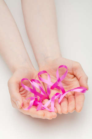 Caucasian female hands holding many pink ribbons, symbols of breast cancer awareness. photo