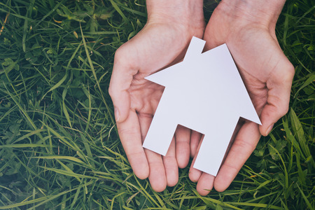 Buy or build a new house - two hands of a woman holding a white cutout house over green grass, viewed from the top. Stock Photo
