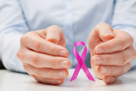 Hands of a young woman around a pink ribbon, international symbol of breast cancer awareness. photo