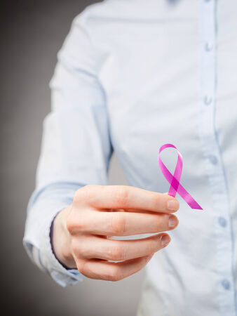 Closeup image of a female hand holding a pink ribbon - symbol of breast cancer awareness.