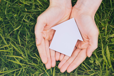 Two female hands holding a small paper family house cutout over fresh green grass. photo