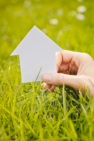 Female hand holding a small paper cutout house over a fresh green grass field. photo