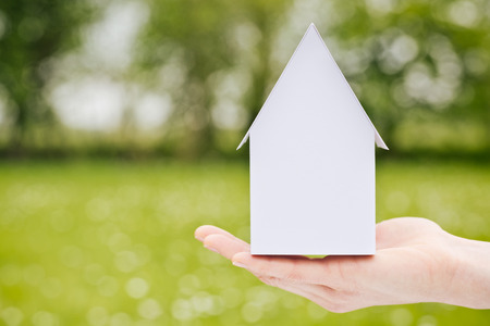 Hand of a woman holding a small white paper model family house before a large empty green field  photo