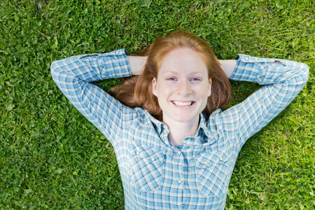 lies down: Happy young woman lies down over green grass, top view.