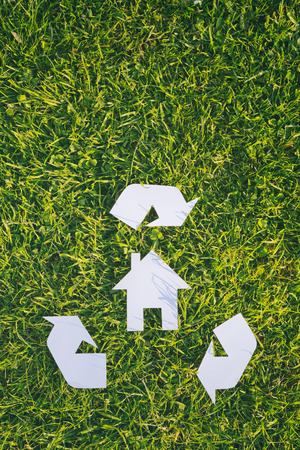 responsibly: Recycle building material or build responsibly - white cutout house and a recycle sign over green grass with copy space. Stock Photo