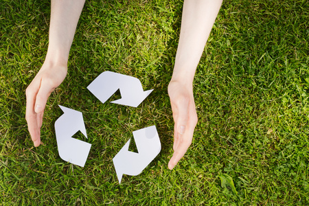 participate: Two female hands surround a recycling sign over a grass background. Top view.