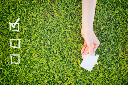 do: Check list for buying a new house or property with a hand holding a white house over green grass. Stock Photo