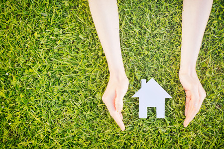 property: Real estate concept - hands of a young woman surround a white cutout house over green grass, copy space available.