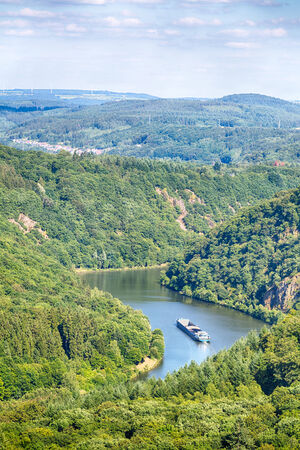 saar: A cargo ship sails through the Saar river in Germany between wooded hills near the city of Mettlach. Stock Photo