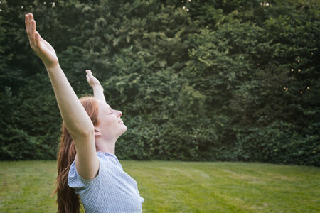 Portrait of a free and happy young woman expressing her joy at an outdoor park. Stock Photo