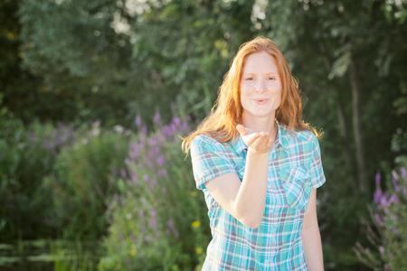 Happy young woman in an outdoor summer garden blows an air kiss toward the camera. photo