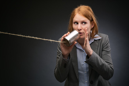 Young businesswoman tells a secret or shares confidential information through a can and a string phone.