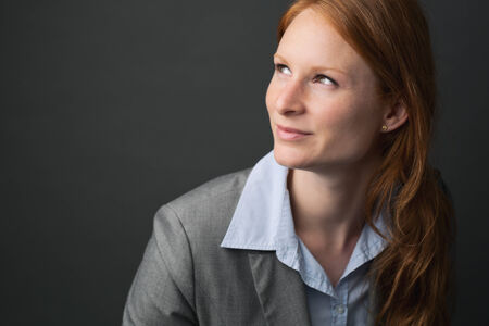 Closeup portrait of the face of a young businesswoman with red hair in a grey suit. photo