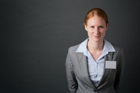 name tags: Smiling young corporate businesswoman wearing a blank name tag poses before a dark background with copy space.