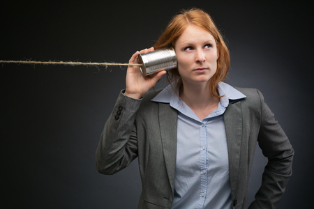 Young corporate business manager or leader listens carefully on a can and a string phone before a dark background with copy space. photo