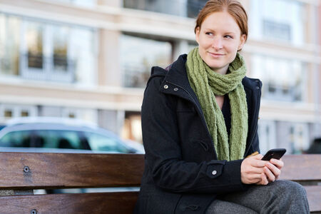 A young woman looks to her side and smiles as she types a text message or works on her mobile phone. Photographed in the Fall on a city street. Stock Photo