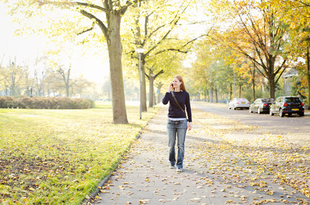 sidewalk talk: A happy young woman walks on a sidewalk near a city park while talking on a mobile phone. Photographed in the Fall or Autumn.