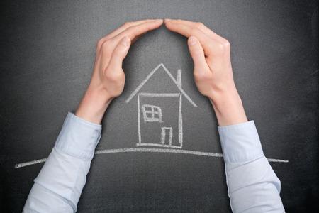De handen van een jonge zakenvrouw of huiseigenaar te beschermen een krijt huis getrokken op een schoolbord. Stockfoto - 34895603