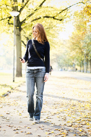 sidewalk talk: A casual young woman looks at a mobile phone while walking on a city street in the Fall or Autumn season. Stock Photo