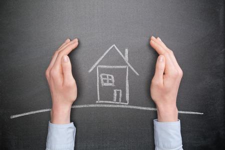 Bescherming van de woning of verzekering concept - het bedrijfsleven de handen te beschermen een krijt huis op een schoolbord. Stockfoto - 35345564