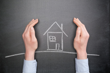 home insurance: Home protection or insurance concept - business hands protect a chalk house on a blackboard.