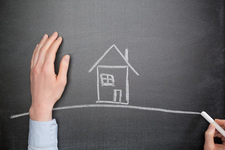 envision: Real estate concept - the hand of a young businesswoman draws a house with chalk on a blackboard.