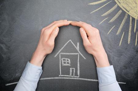 若い実業家や住宅所有者の手は、暑い太陽の下から家を守る。