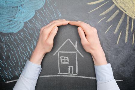 Een jonge zakenvrouw beschermt een huis uit de elementen - regen of storm en zon. Schoolbord tekening, bovenaanzicht. Stockfoto