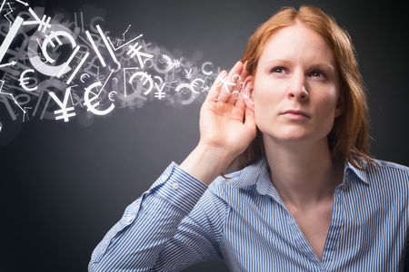financial market: A young businesswoman listens to stock or financial market information - different signs and symbols flow into her hear.