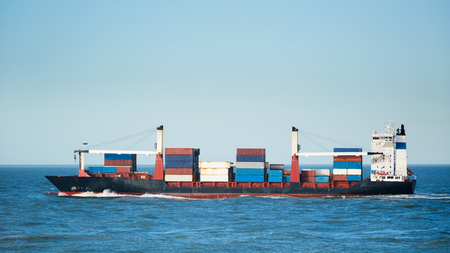 water transportation: A container ship transports containers. Photographed at sea under a clear blue sky.