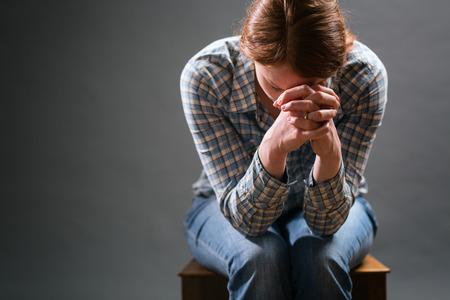 Een jonge vrouw zit op een oude houten stoel in het gebed onder dramatische licht.