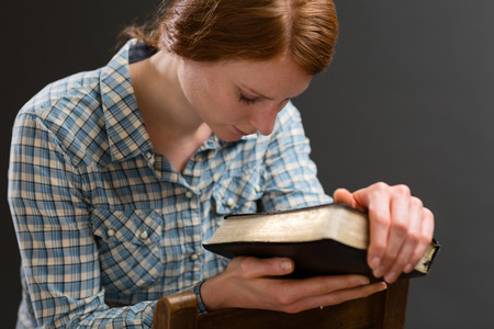 A woman sits on an old wooden chair with a Bible in her hands and prays to God.