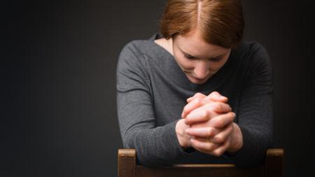 orando: Una mujer se sienta en una silla de madera y ora a Dios.
