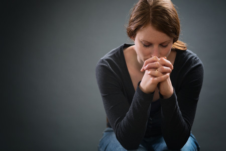 A Christian woman sits on a chair and prays under dramatic light with copy space on the side. Stock Photo