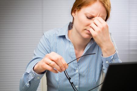 Een vermoeide zakenvrouw opstijgt bril en wrijft haar ogen.