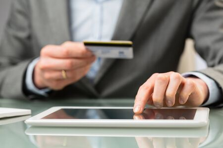 enters: A business person enters credit card information on a tablet computer. Closeup image. Stock Photo